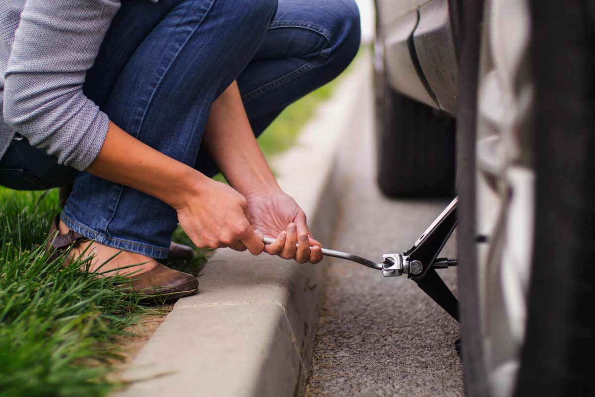woman changing her car's tire